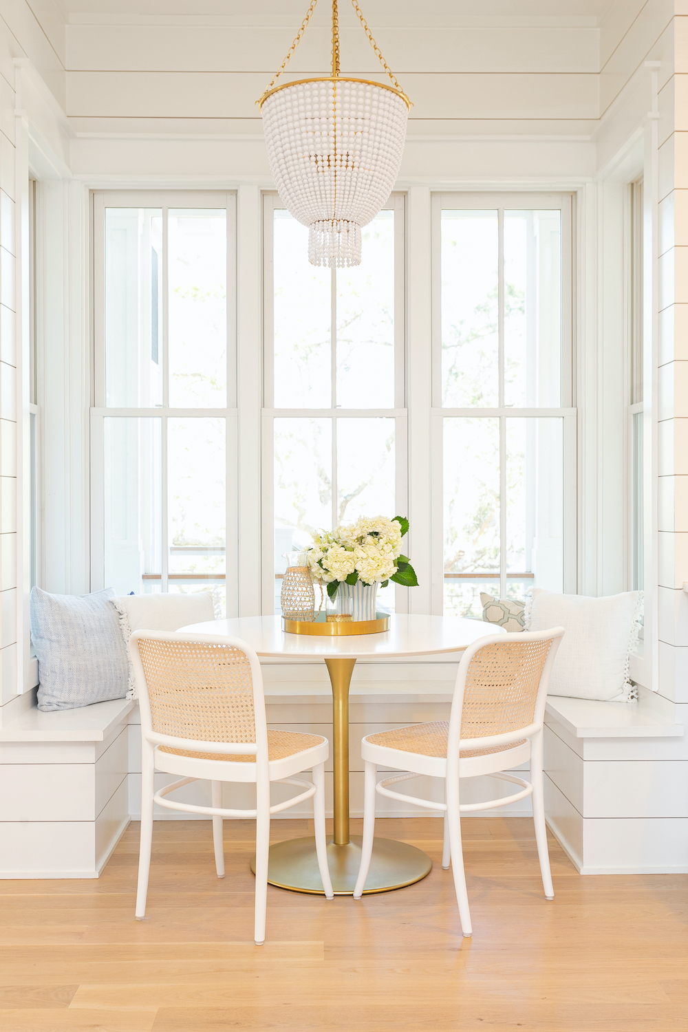Modern coastal home, custom home building, custom home, breakfast nook , kitchen nook, white beaded chandelier, shiplap accent walls, white and gold table