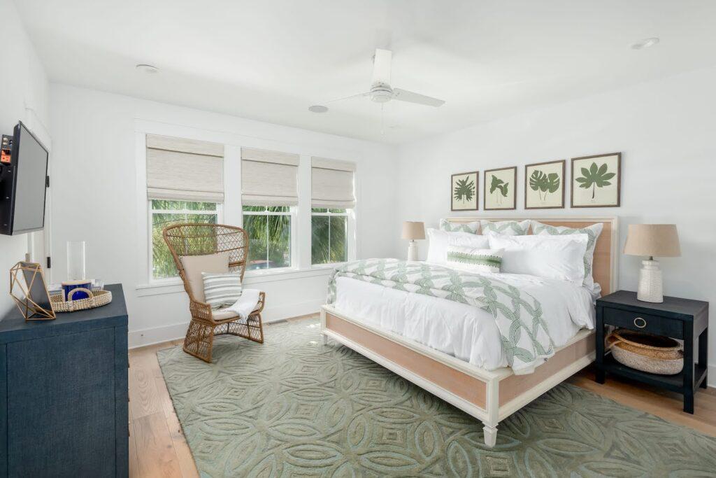 Tropical bedroom, navy blue night table, green and white bedding, custom home, custom builder, Charleston
